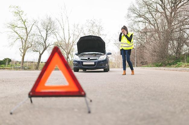 反射警告の三角形が付いている道路で車が故障している間に携帯電話で話している若い白人女性。自動車および道端での援助の概念。
