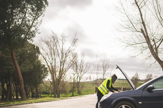 車のエンジン、道路の真ん中で故障した車を見て若い白人女性。自動車および道端での援助の概念。