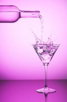 Розовая бутылка разливает жидкость в бокал для коктейля и делает брызги