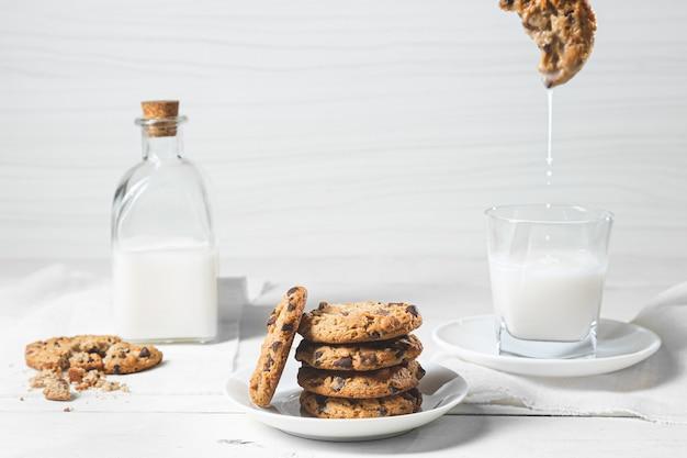 Шоколадное печенье и молоко на белой деревянной поверхности