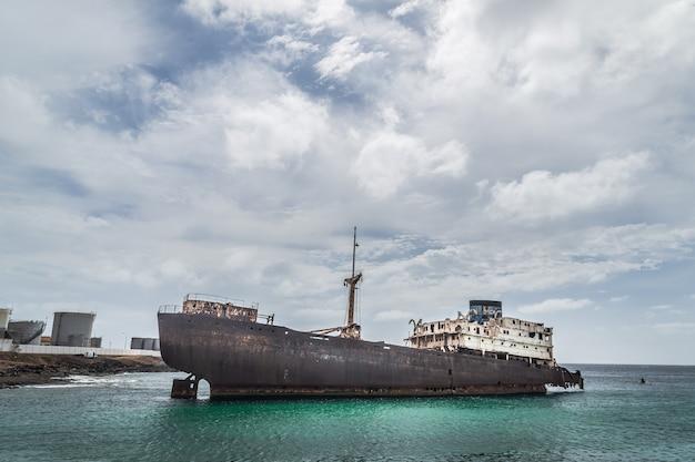 Заброшенный катер в море. облачное небо, бирюзовое море