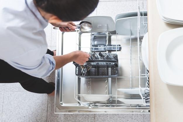 カトラリーを彼女のアパートのキッチンの食器洗い機に置く女性