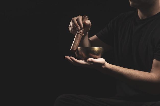 Деталь человека, сидящего играет тибетская поющая чаша в черной одежде на черном