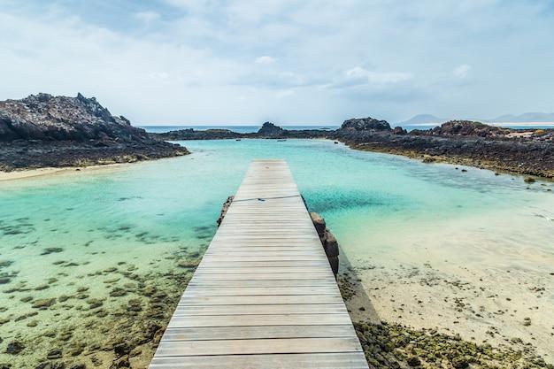 スペイン、カナリア諸島、フェルテベントゥラ島のロボス島の港。火山の海