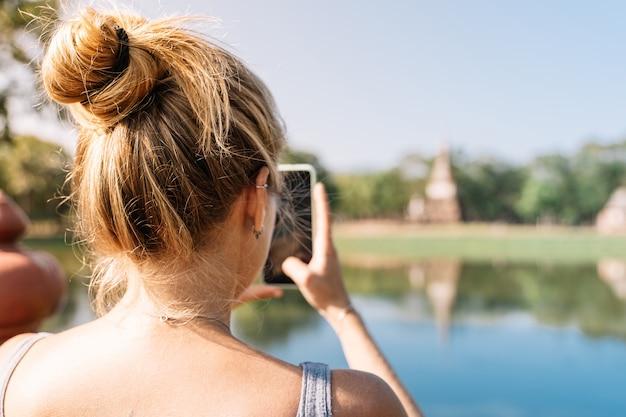 Белокурая девушка фотографируя с мобильным телефоном в природе с не в фокусе