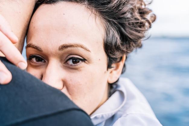 Молодая девушка с вьющимися волосами смотрит прямо перед собой, обнимая своего партнера с расфокусированным морем