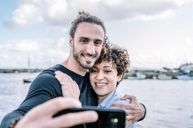 Молодая пара обнимается за плечо, делая селфи с портом и морем не в фокусе