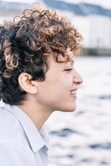 Вертикальное фото девушки в профиль с вьющимися волосами и пирсингом носа, глядя спереди