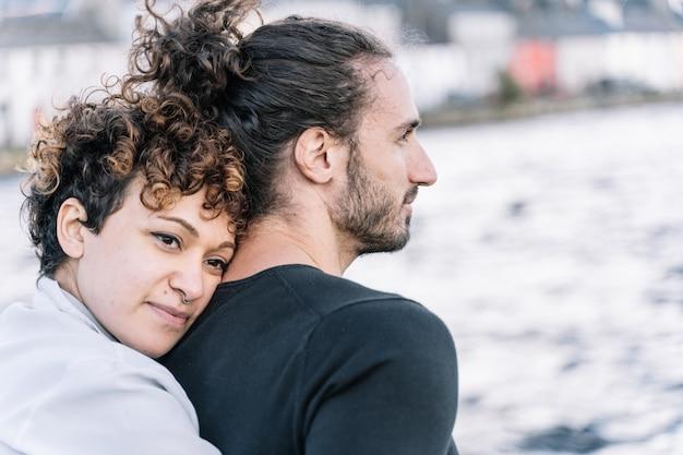 Девушка обнимает своего партнера с морем не в фокусе