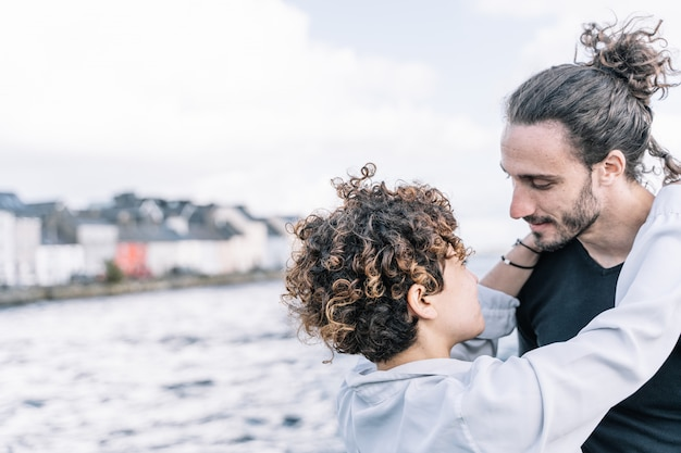 焦点が合っていない海と首でお互いをハグする若いカップル