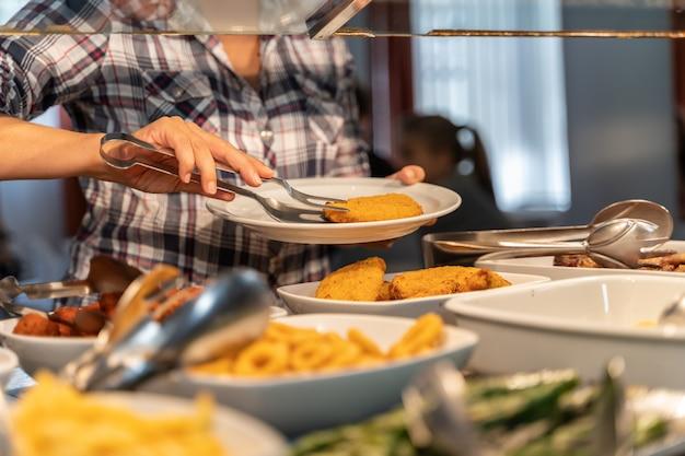 Женщина берет еду из самообслуживания