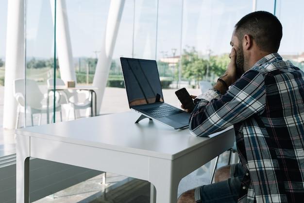 ノートパソコンの前で作業し、ワークスペースで手に携帯電話を持つ男