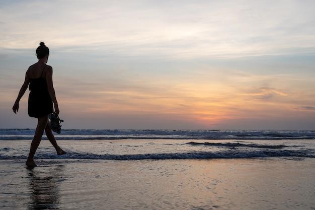 Девушка гуляет по воде на пляже