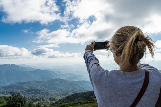 山の地平線ビューの携帯電話で写真を撮る金髪の女性