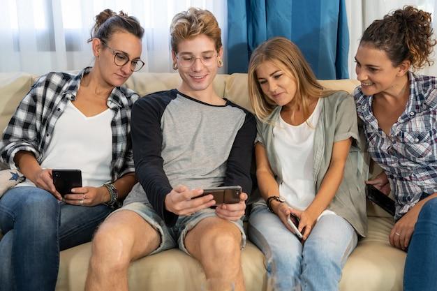 Мальчик с пирсингом, улыбаясь, показывая экран мобильного телефона рядом с группой людей на диване