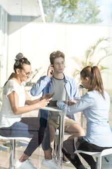 Группа молодых людей, использующих свой мобильный телефон на коворкинге