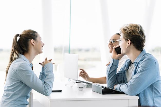 ノートパソコンとテーブルで携帯電話を使用してテーブルに座っている若い人たちのグループ