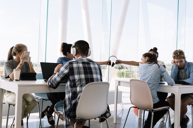 Две девушки в шлемах сидят за рабочим столом с другими людьми в коворкинге