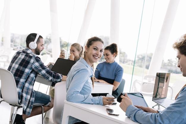 Молодая девушка с кофе в руке обернулась перед столом с другими людьми, работающими