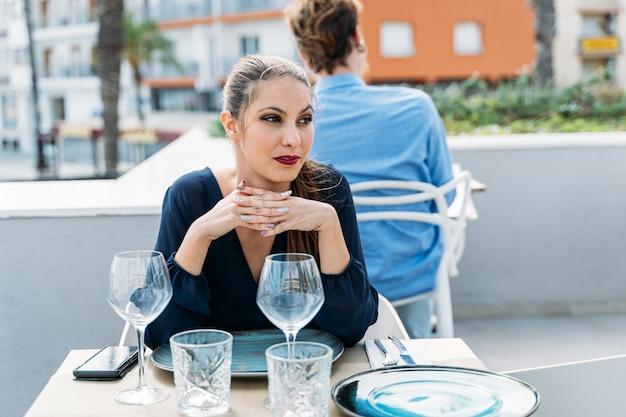 Молодая девушка сидит за столом в ресторане под открытым небом