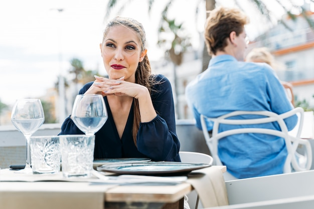 Скучная молодая девушка ждет своего свидания, сидя за столом в ресторане под открытым небом