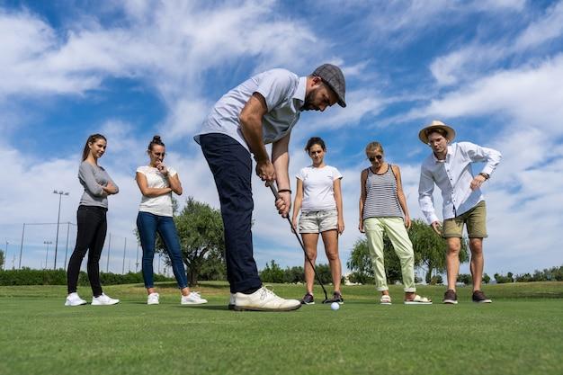 Молодой человек с беретом играет в гольф с гольф-клубом перед группой людей
