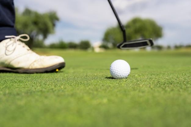 ゴルフコースでゴルフボールと人の靴