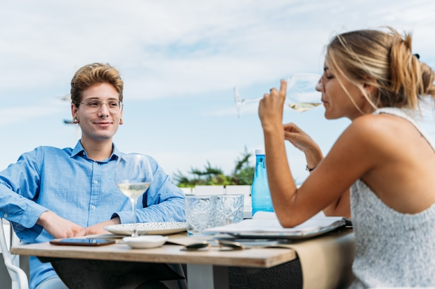 ビーチフロントのレストランのテーブルに座ってワインを飲む金髪の熟女を見て若い男