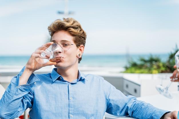 テラスで白ワインを飲むピアスを持つ男