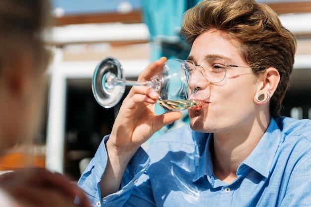 Мужчина с пирсингом пьет белое вино на террасе