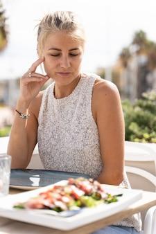 Женщина смотрит на салат с лососем, сидя за столом с бокалами в ресторане