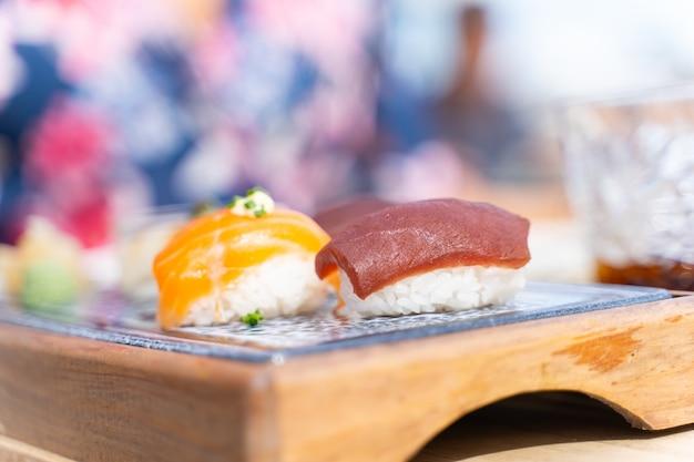 木製の小さなボードで提供されるマグロとサーモンの寿司料理のセット