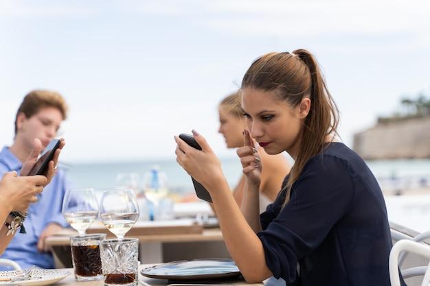 Молодая женщина, используя экран смартфона как зеркало для макияжа, пока сидит на террасе ресторана