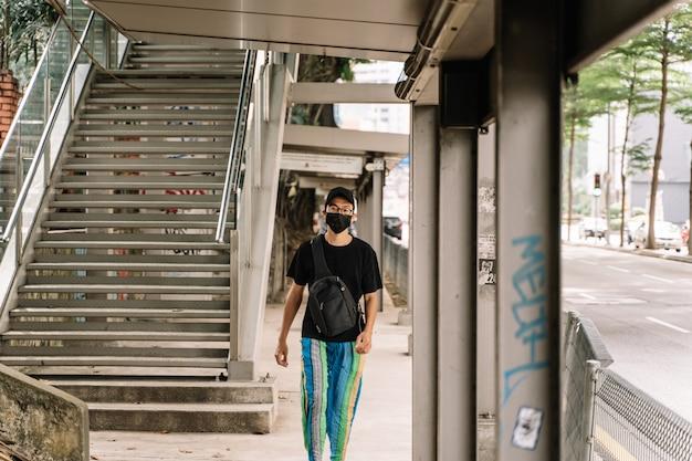 黒い顔のマスクを着ているアジアの少年