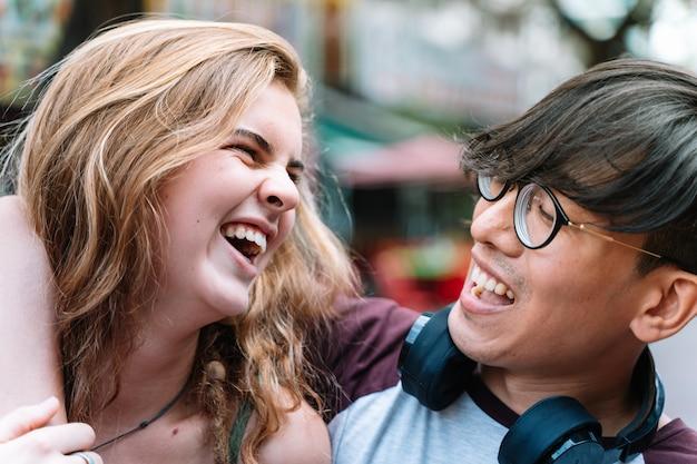 Китайский мальчик и кавказская девушка, глядя друг на друга, смеясь и обнимая