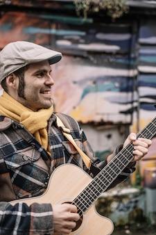 男は通りに立って、アコースティックギターを演奏します。