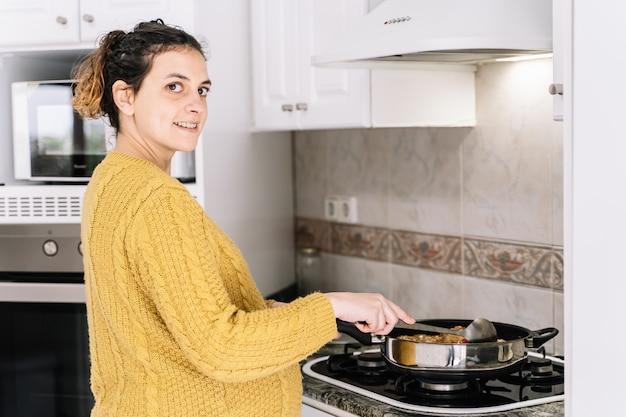 妊娠中の女性が笑顔のキッチンで立っている黄色のセーターを調理