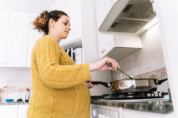 黄色いセーターを調理している妊娠中の女性の対位の写真