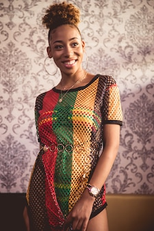 ヴィンテージの装飾が施された壁の前で笑っているカラフルなネットドレスの黒い少女