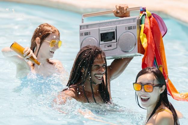 Люди танцуют в бассейне с бутылками пива