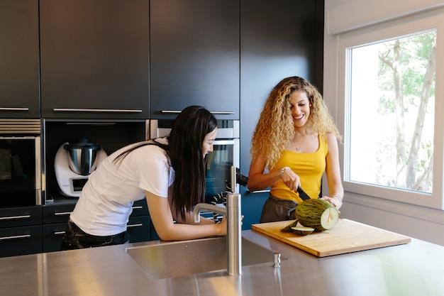 彼女の友人が台所の中のカメラで彼女を撮影している間、巻き毛のメロンを切るブロンドの女性