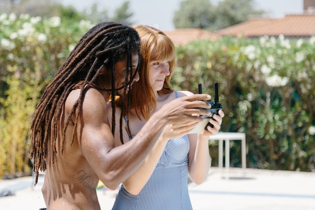 Многокультурного пара в купальнике стоя в бассейне с помощью пульта дистанционного управления
