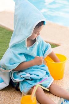 プラスチックのバケツとオレンジジュースをプールで遊んでフード付きタオルで座っている子供
