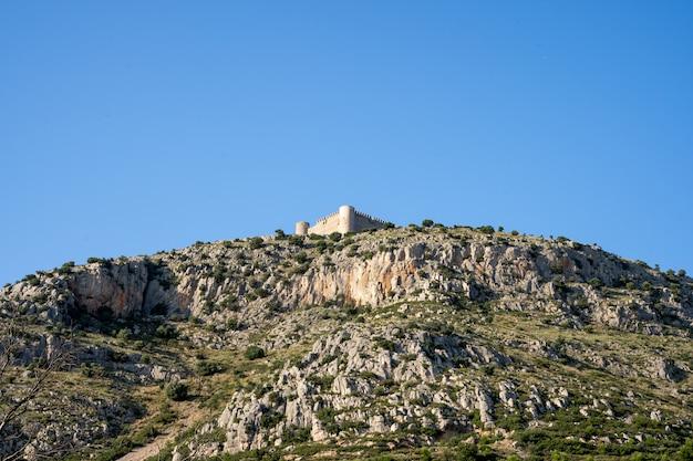 Замок на вершине горы, полной скал. замок торроэлья де монтгри