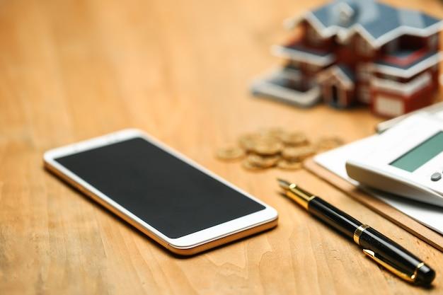 家のモデル、スマートフォン、計算機と木製のテーブルの金貨