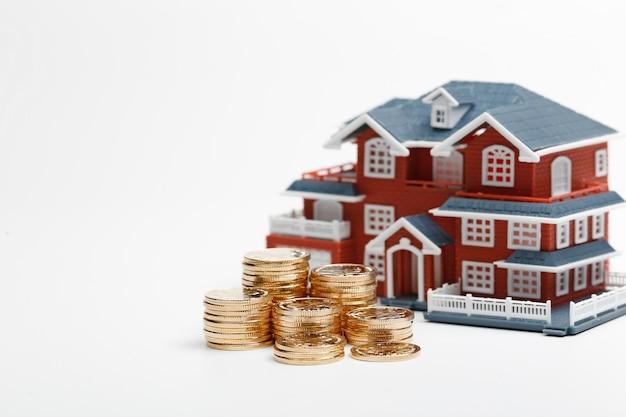 Монеты юаней, уложенные перед моделью жилья (цены на жилье, покупка жилья, недвижимость, концепция ипотеки)