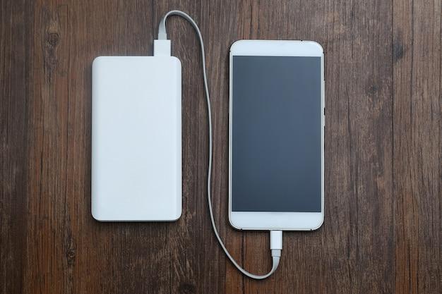 木製テーブル上のパワーバンクと携帯電話