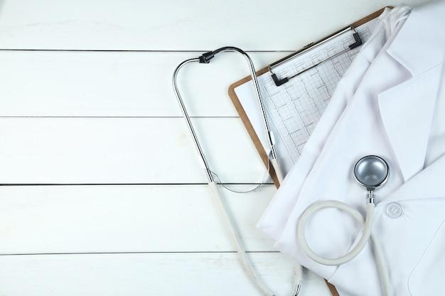 聴診器、クリップボード、白いきちんとした木製の机の上にある医者の制服