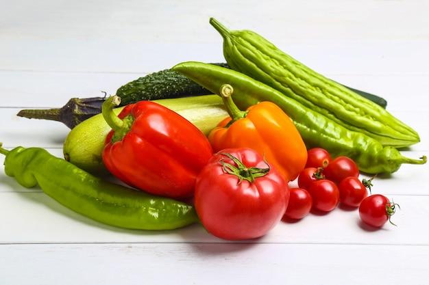 白い木のテーブル上の様々なカラフルな野菜