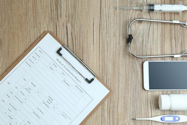 木製の机の健康診断レポート、携帯電話、医療機器の上面図